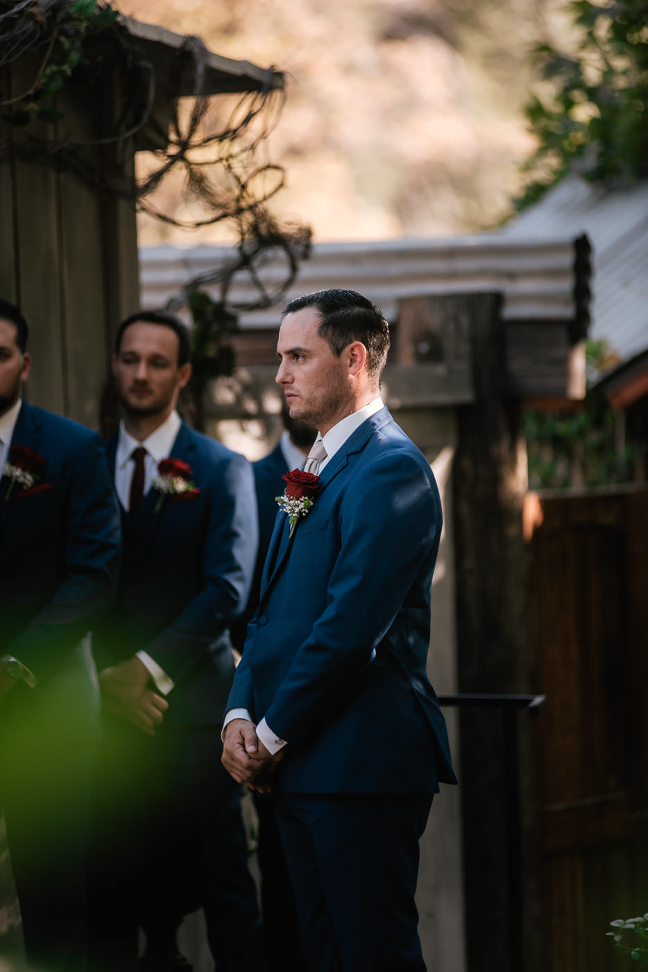 Groom wears a stylish blue suit at his marriage ceremony.