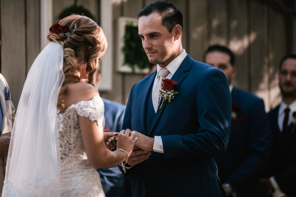 Groom holds his brides hands and listens intently to her marriage vows.