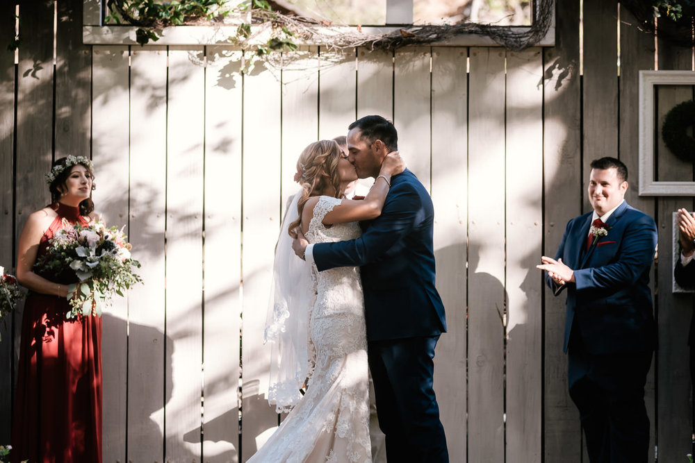 Romantic first kiss at this rustic wedding at The Homestead at Wilshire Ranch.