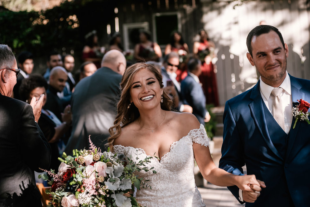Newlyweds are all smiles as they exit their ceremony.