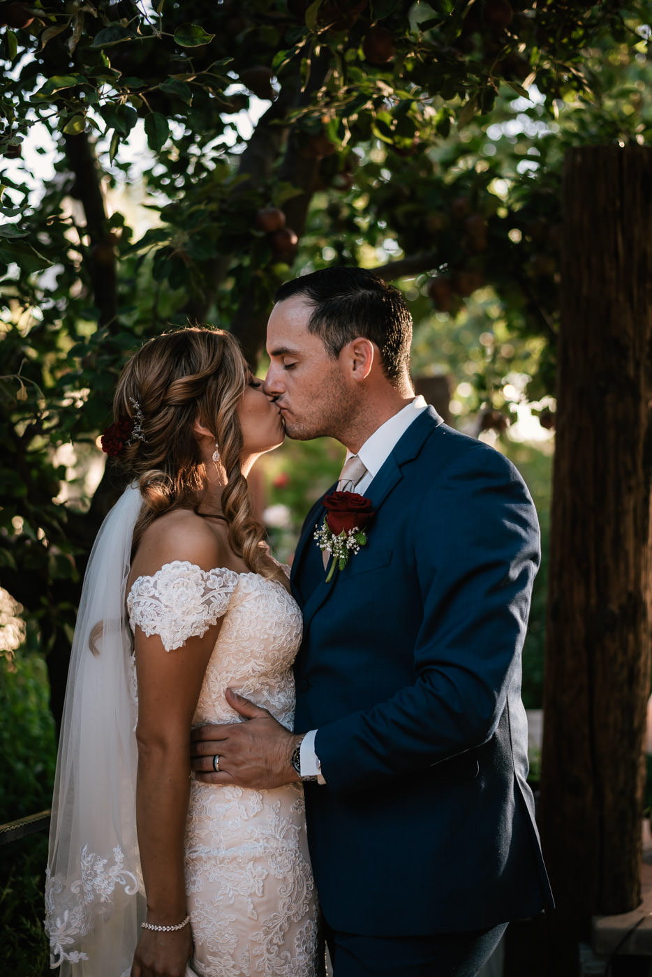 Passionate kiss under the apple tree at this rustic wedding in Oak Glen California.