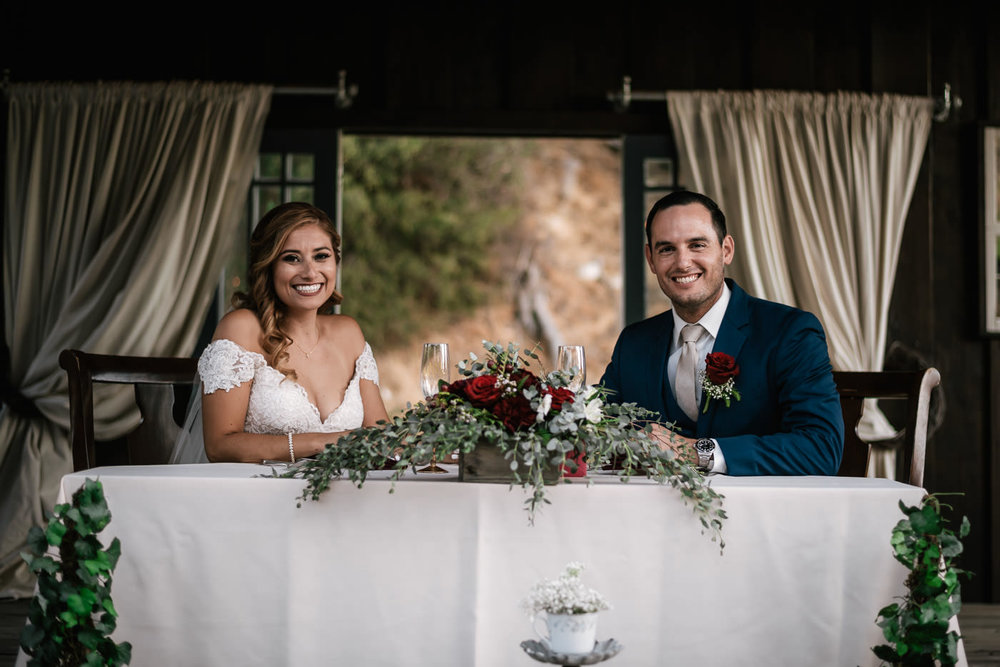 Bride and groom take a seat at their sweetheart table and prepare to eat at their reception.