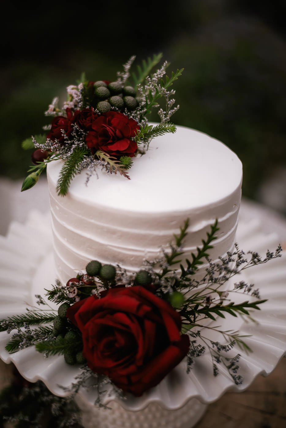 Simple white wedding cake with red rose details and other splendid greenery.