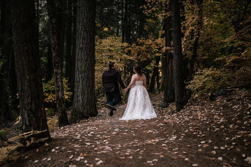 Groom jumps and clicks his heels together with joy as he walks with his new bride through the forest, captured by their elopement photographer.
