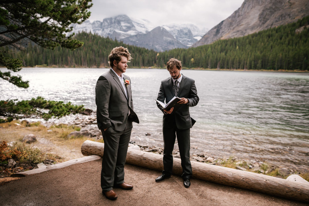 Officiant stands with the groom as they wait for the bride to arrive for the ceremony.