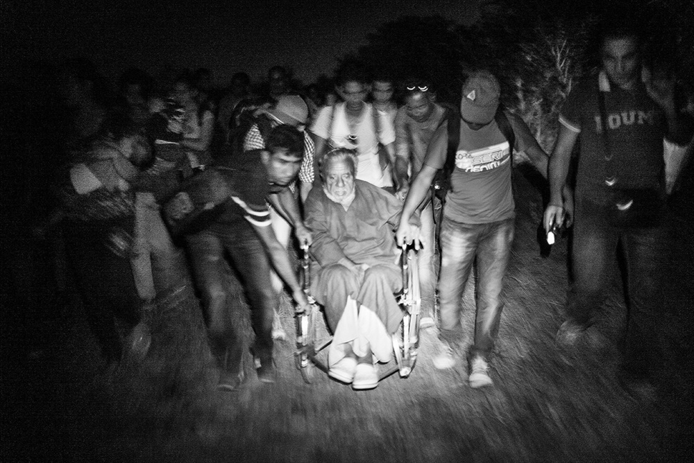 Faiz is quiet while the large group of men pushes the wheelchair over the border into Hungary at the small crossing point near Röszke on September 2nd 2015. Shortly after the front wheel of the wheelchair gets stuck once again in one of the many holes in the small gravel road. Faiz hand squeezes the armrest extra tightly while the men around him struggle to get the chair free.