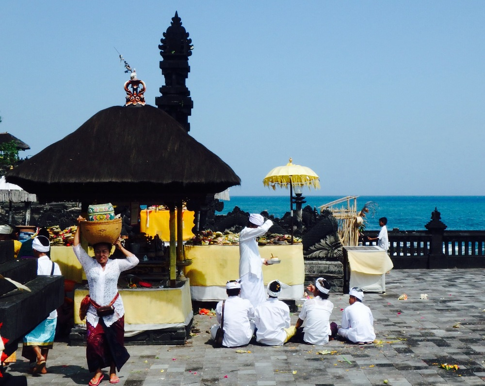 Offerings are prepared nearby while others receive blessings.
