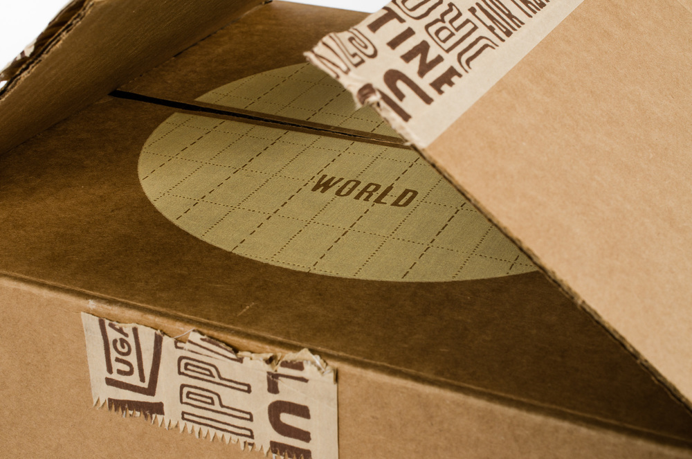 "A very intentional ""unboxing experience,"" this photo gives a peek into the pacing using customized shipping tape. The revealed ""One World"" screen printed image then opens to a cardboard insert that highlights the products of that particular box."