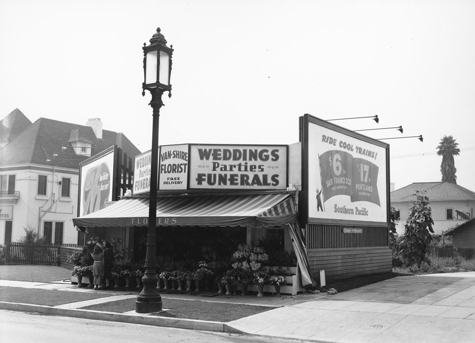 Wilshire Special Street Lights in front of florist shop, south side of Wilshire where Wilshire Park Elementary School's staff parking lot is currently located. The French Eclectic style house in the background still stands, built and still owned by the Neville family. If the light bases look familiar, it is because they are still in use today.