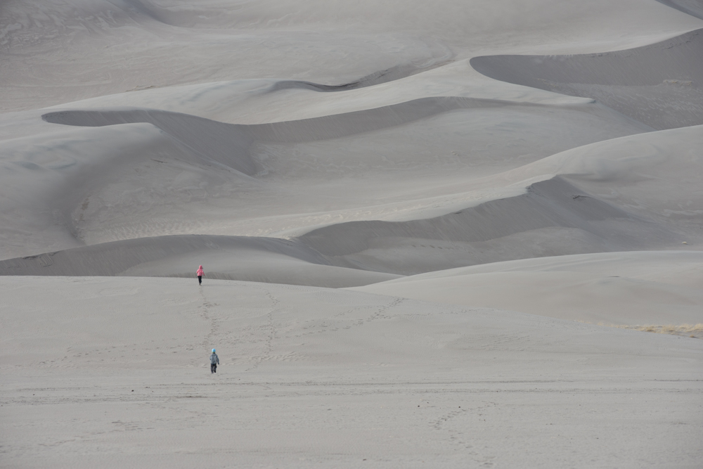 kids running in the  great sand dunes