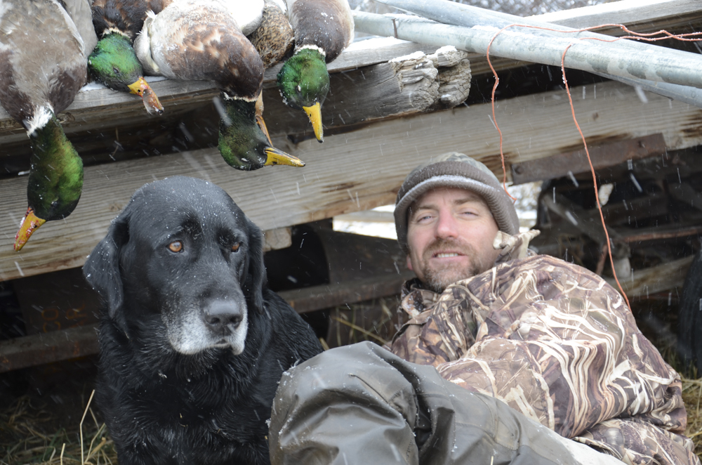 A duck hunter, his dog, and a day's feast