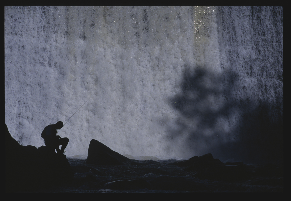fly fishing near a waterfall