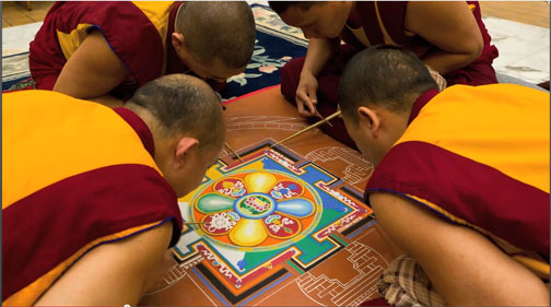 Tibetan monks creating a sand mandala.  Source: https://gandenmonkstourpgh.wordpress.com/tibetan-buddhist-ritual-arts-practices/