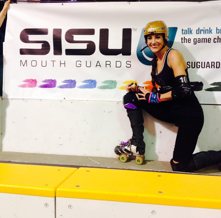 Brawlstars skater Bex poses next to the SISU banner at our home bout at Buhr Park, June 7, 2014. / Photo courtesy SISU