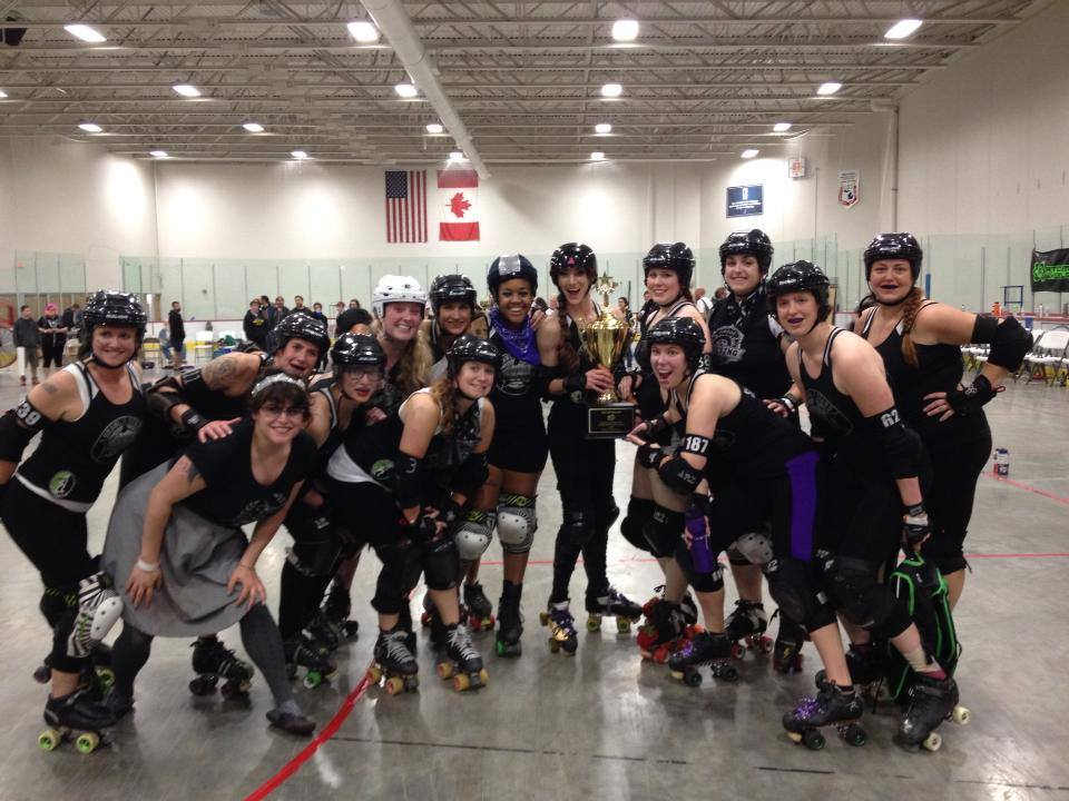 Ann Arbor Brawlstars, Mitten Kitten 2013 champions, pose with their trophy.