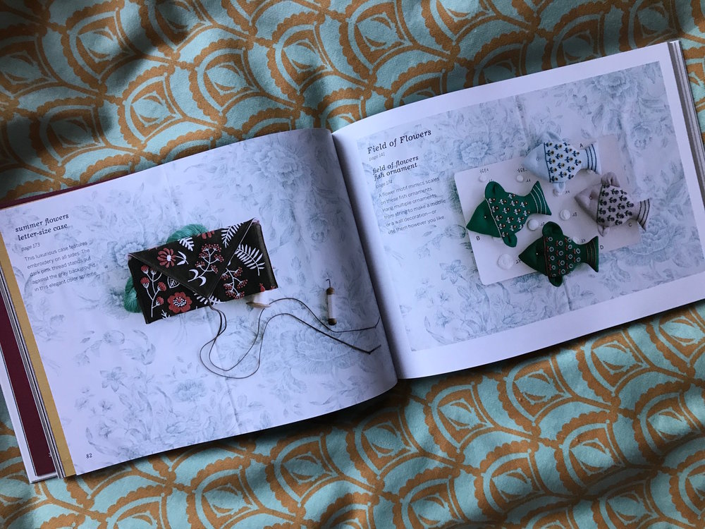 A beautifully embroidered envelope clutch and fish ornaments.