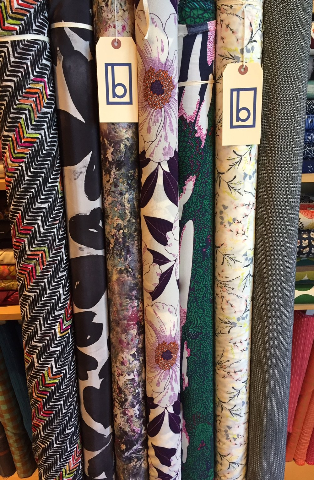 Some really interesting and gorgeous pieces in this here pic! On the far left is a rayon knit gauze that is so lovely and delicate, with a bold colored design. A couple of silks, large floral poly crepe with detail so sharp, three rayons, the third in from the left is an incredible jungle print in navy, kelly, fuchsia and white, striking!