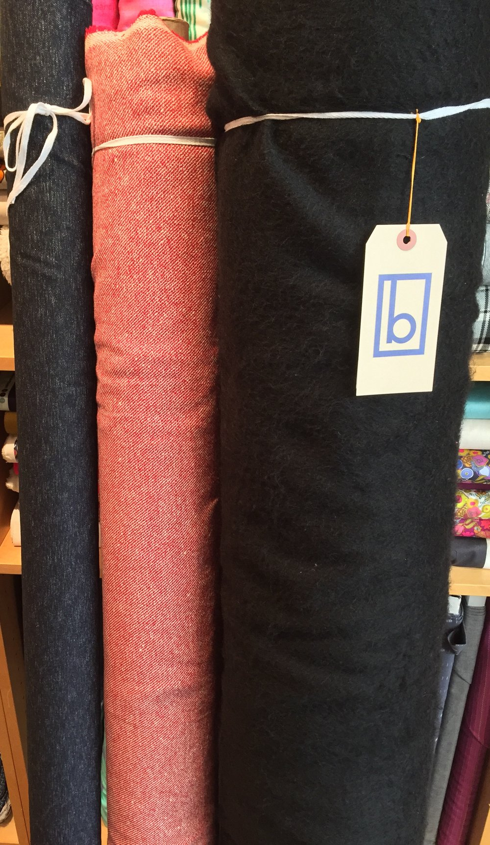 More wool blends: navy wool stretch tweed, red twill, and black acrylic fuzzy blend.
