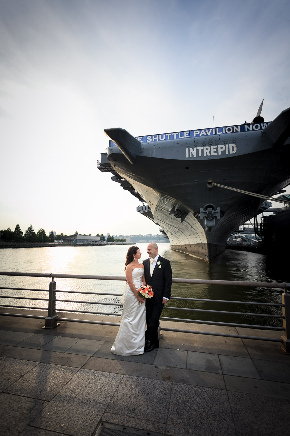 A gorgeous wedding photo of Jane and Larry in front of the Intrepid on the Hudson River.