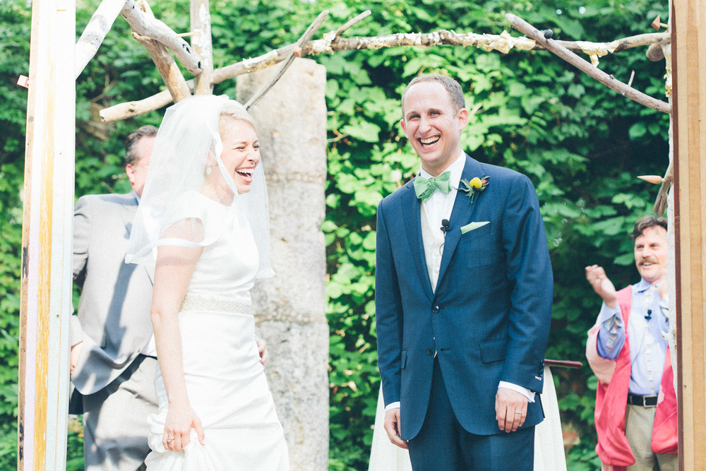 Hooray! We're married!! Now what do we do? Bride and groom smile as their status as a married couple becomes official.
