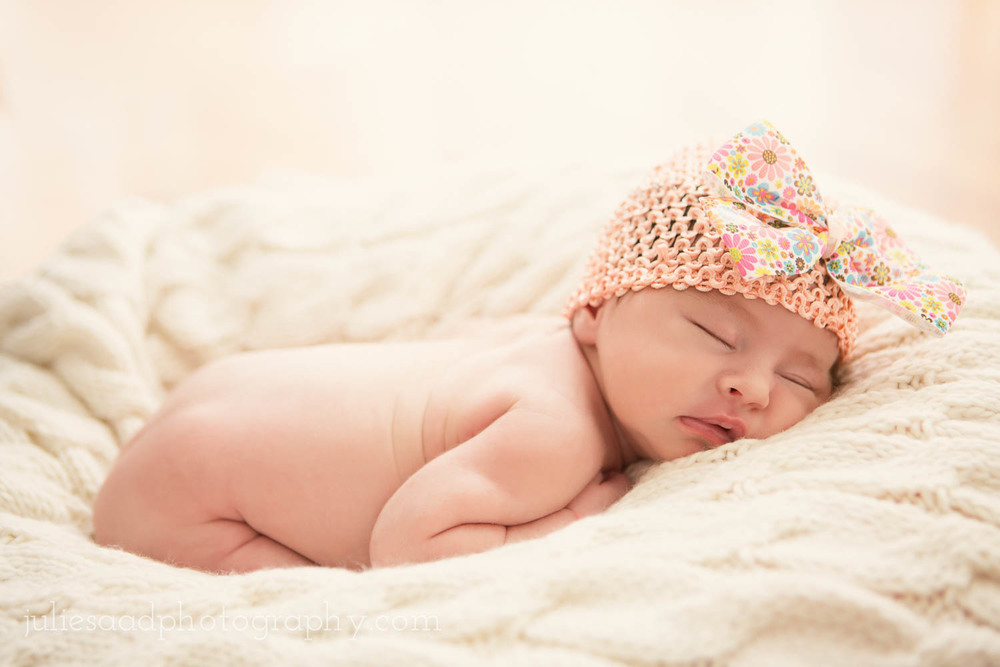 Newborn baby girl sleeping with pink hat and bow.