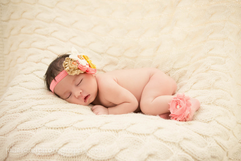Sleeping baby girl with flower headband and pink flower bear feet shoes. Adorable newborn photograph by fine art photographer Julie Saad.