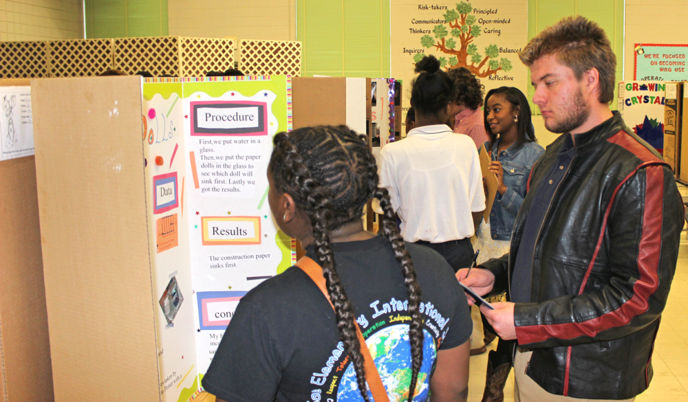 MSMS Junior Adam Stewart takes a look at a Sale fourth grader's science fair project.