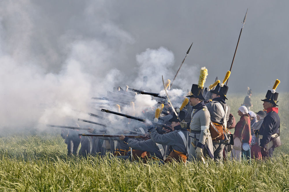 Soldiers in front of the wood of Hougoumont during the reenactment of the battle of Waterloo (1815), June 2011, Waterloo, Belgium, via Wikipedia.