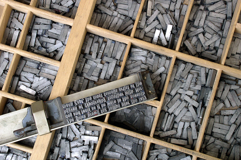 Movable type sorted in a letter case and loaded in a composing stick on top, by William Heidelbach via Wikipedia.