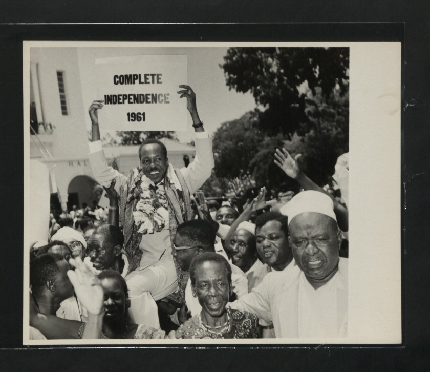 Julius Nyerere holding a sign demanding complete independence from the British Empire in 1961, Photo from the National Archive via Wikipedia.
