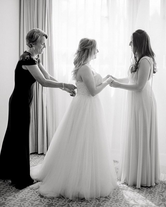 Sweet moment shared between the mother of the bride and sister as they beautifully helped Alexa into her wedding dress!