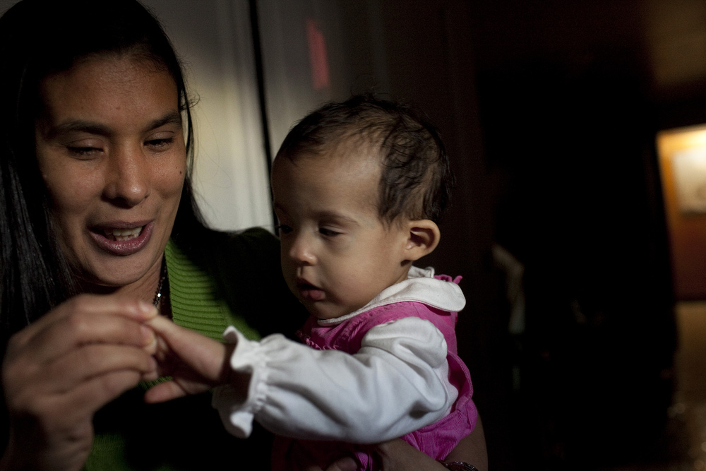 Yugely Nunez, who was born blind, holds her one-year-old daughter Yumely Nunez who inherited her mother's blindness in the foyer of their basement apartment.