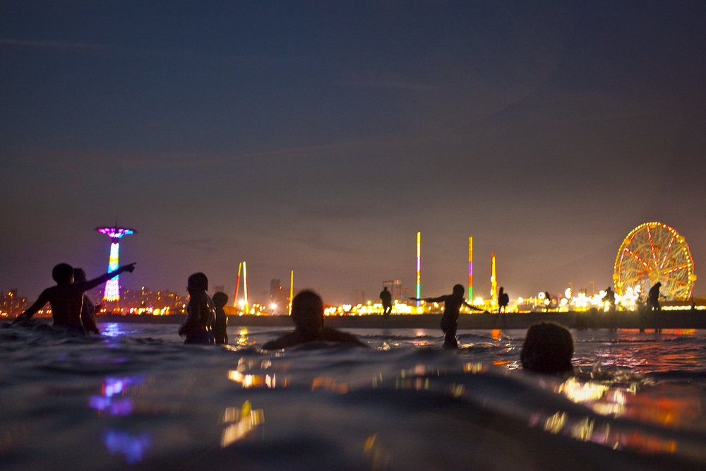 Night swimmers at Coney Island remain in the water as Labor Day weekend begins bringing with it an unofficial end to the summer.