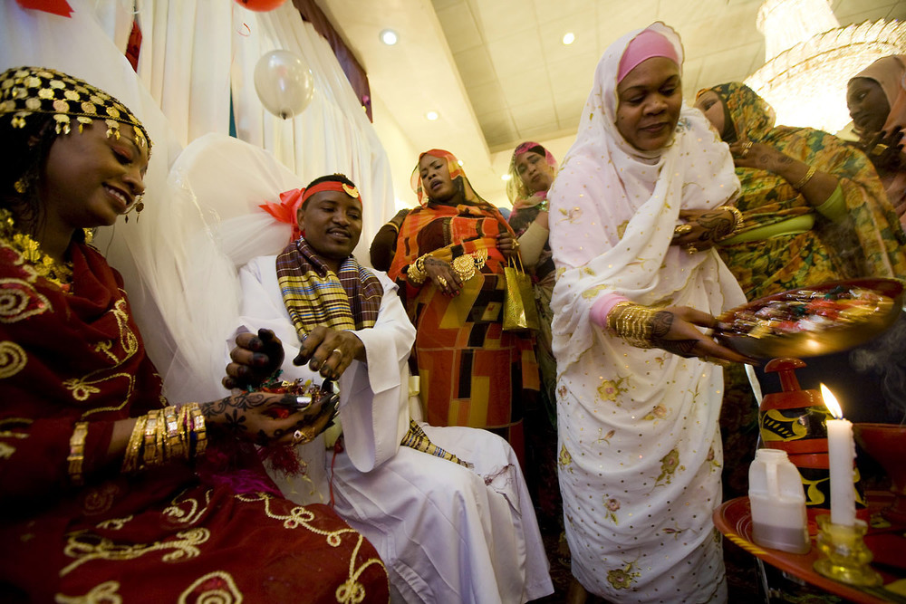 Fatimah Mohammidin, left, and her husband, Yassir Haroune, center, are married during a celebration at the Gourmet Banquet Hall in the Kensington neighborhood of Brooklyn. The couple were engaged in Darfur in 2006.