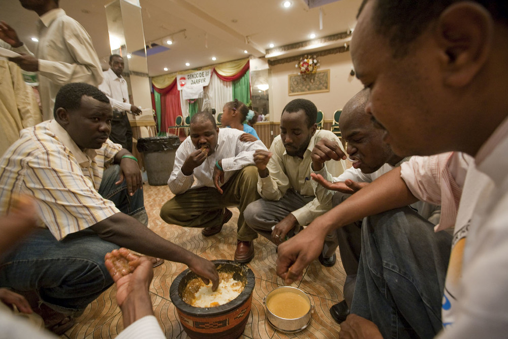 Darfurian immigrants come together to break the day's Ramadan fast. The wooden catou is wrapped in a braided fabric called a mandala and filled with assida, a thick porridge made from ground millet and okra, a staple in Darfur.