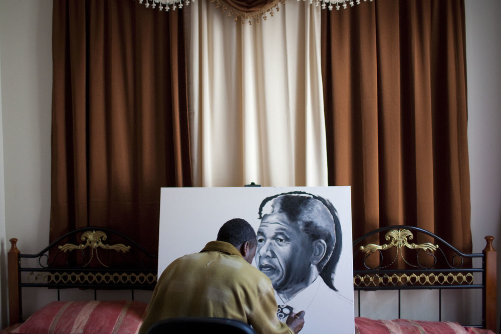 Abdallah Abaker, 37, who came to the United States from Darfur in 2001, works on a painting of Nelson Mandela. Mr. Abaker paints when he is not driving a taxi, which he does 13 hours a day, seven days a week.