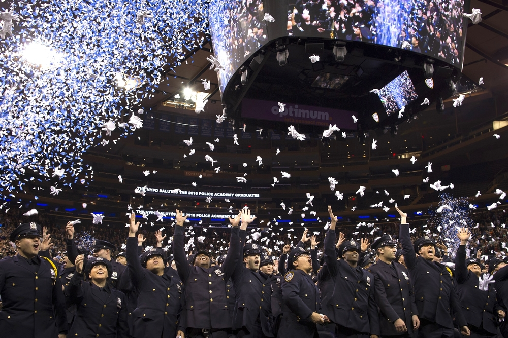 New police officers throw their gloves in the air at the conclusion of a graduation ceremony at Madison Square Garden in New York City.