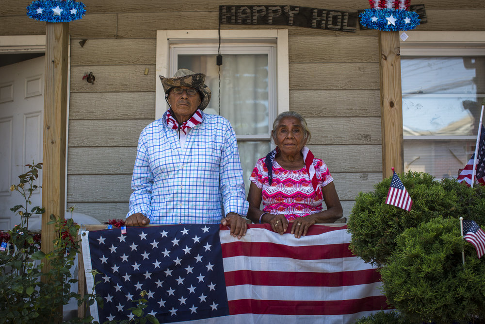 A Staten Island couple watch as a July 4 parade goes past their home.