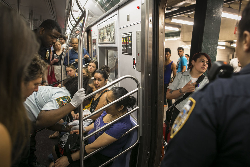 Police and EMTs attend to a sick subway passenger in Brooklyn.