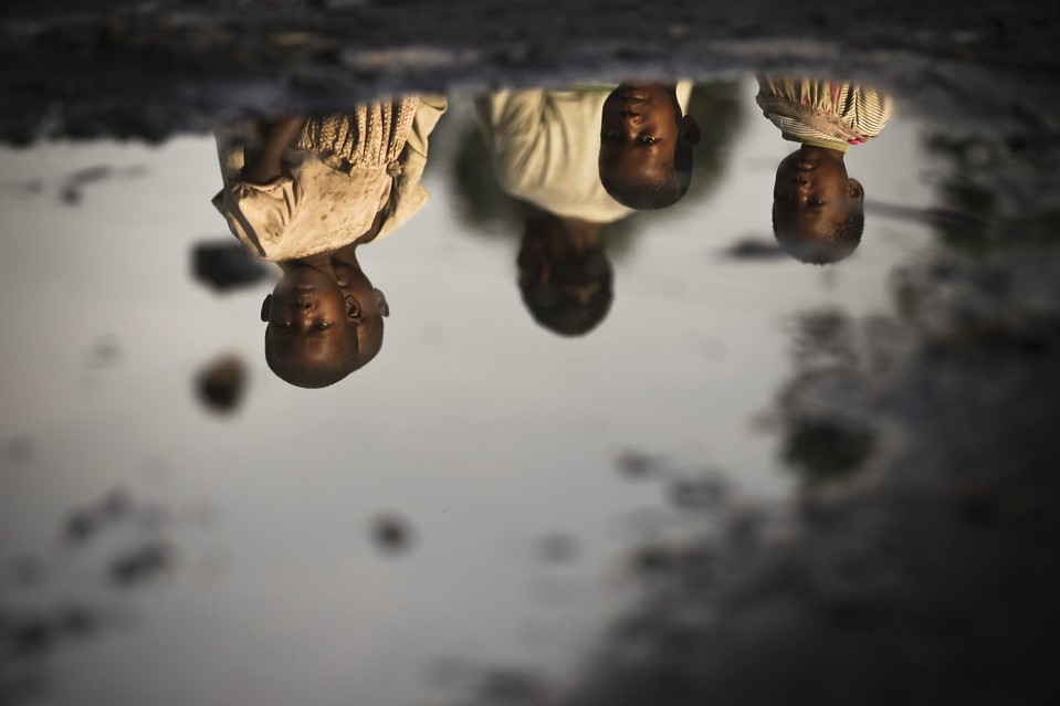 Children were reflected in a puddle at the Mugunga camp for internally displaced people near Goma, Congo on Nov. 28, 2012.   [Credit :    Dai Kurokawa/European Pressphoto Agency   ]