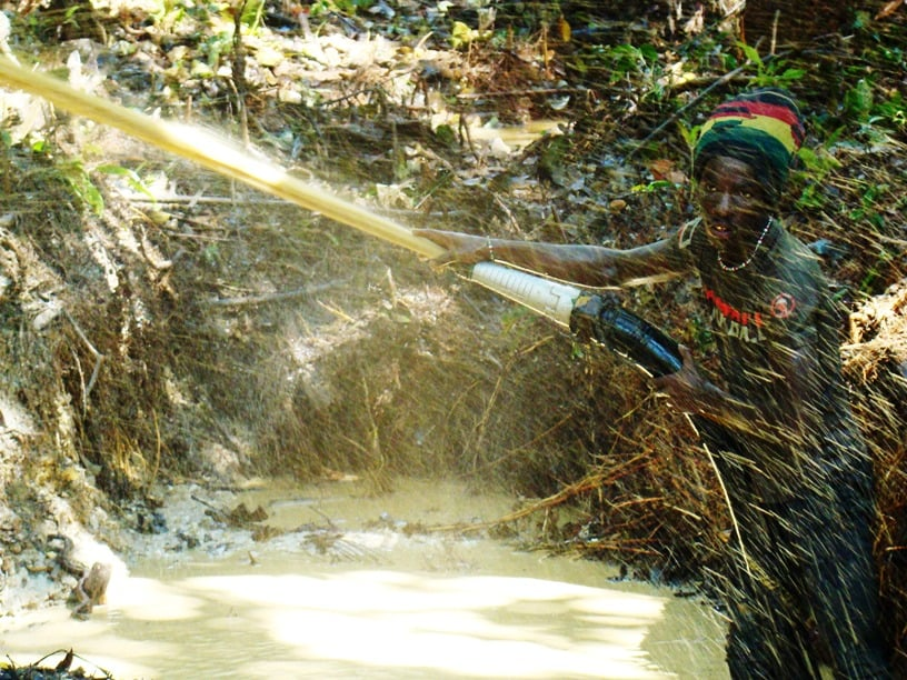 An illegal gold miner scours the forest soil  (photo by William Laurance)