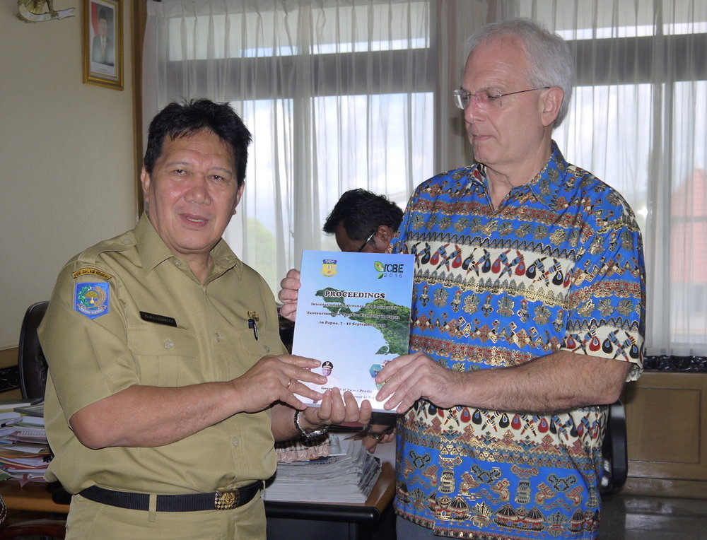 Assistant Governor Elia Loupatty presents the Papua government's plan outlining its conservation pledge to ALERT director Bill Laurance (photo by Mohammed Alamgir)