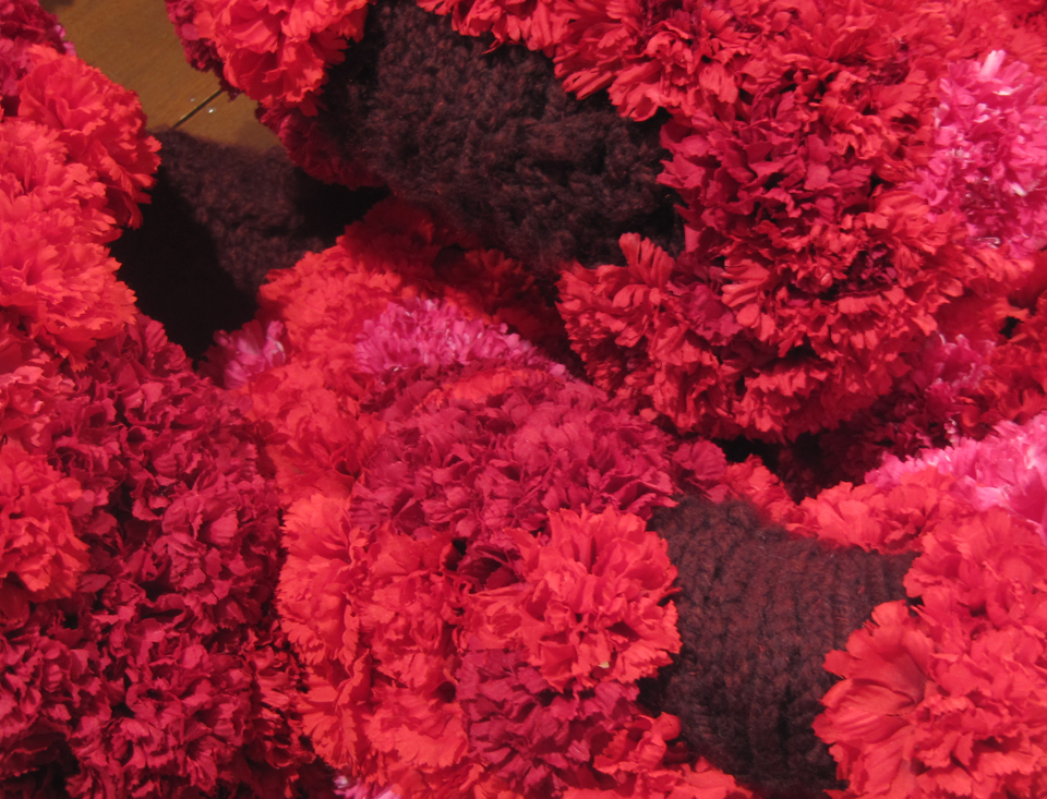 Detail,  The Dreaming,  yarn, silk carnations, wooden table. dimensions variable, 2012.
