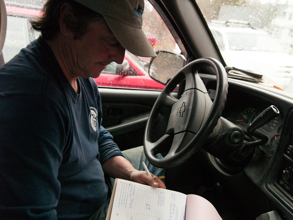 (04/22/09) Carter Newell checks his records while making mussel deliveries.