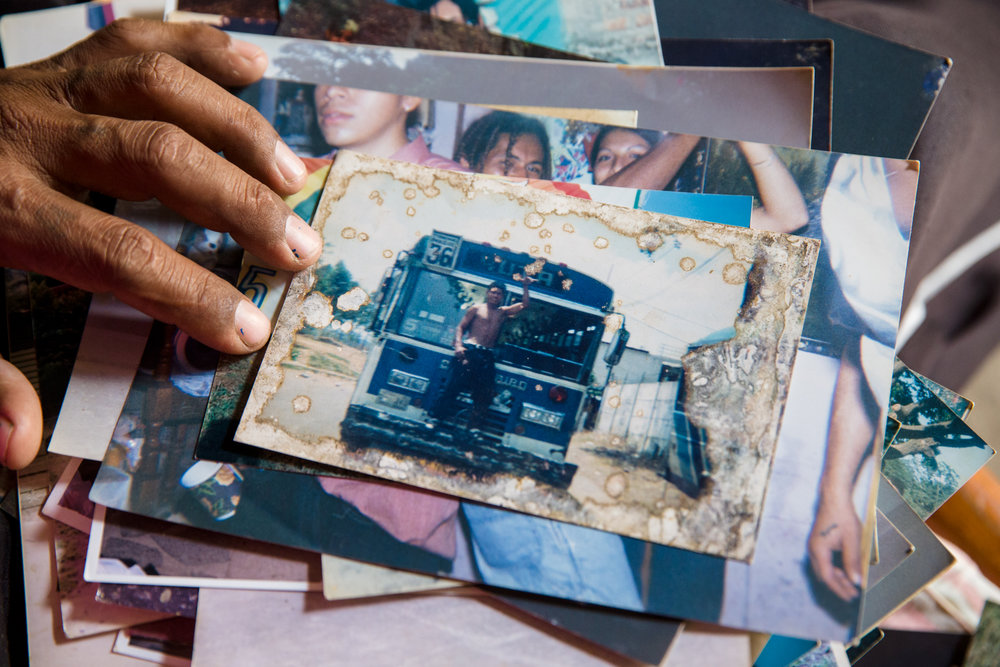 "Jairo Blanchard looks through a stack of old photos from when he was a gang member. He comes to one of himself posing in front of a bus. ""That was my bus"" he says. ""I controlled that bus line,"""