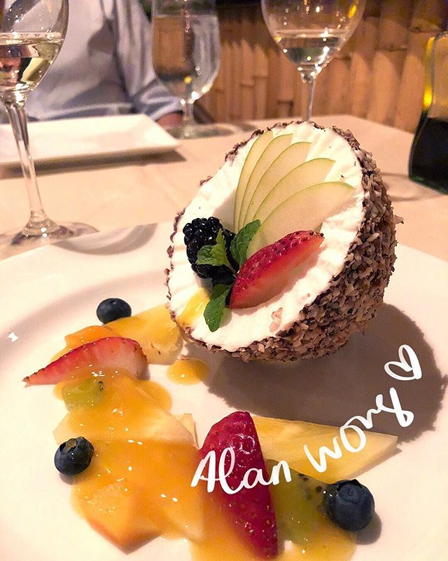 "Every year we go to Hawaii, and every year I eat the Alan Wong ""coconut"" 🌴 Coconut sorbet in a dark chocolate shell covered with toasted coconut flakes, topped with fresh fruit 🌺 So pretty, and I love the details -- if you look closely, the sorbet is shaped to have ""ridges,"" just like a freshly cracked coconut! @alanwongs"