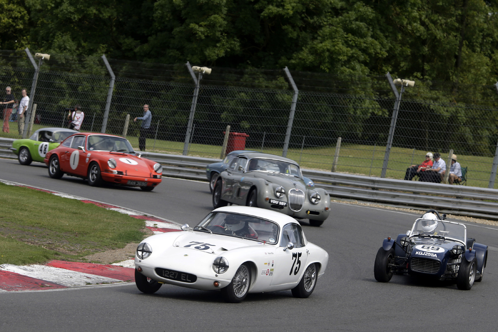 Robin Ellis makes good his escape whilst Brian Arculus, almost hidden, is held off by the Paul De Havilland Jaguar XK150. Photo - Gary Hawkins