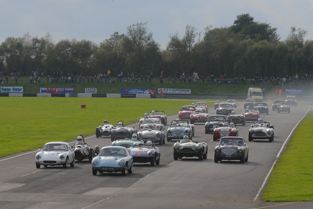 A grid that would grace any meeting - yes, even Goodwood Revival or Silverstone Classic. Brian Arculus gets the jump on poleman Robin Ellis whilst Simon Hadfield (Elva) and John Ure (Cooper Bristol) burst through from the third row but best start of all is surely Mike Thorne in the Austin Healey from the 4th row!       Photo - Ollie Read