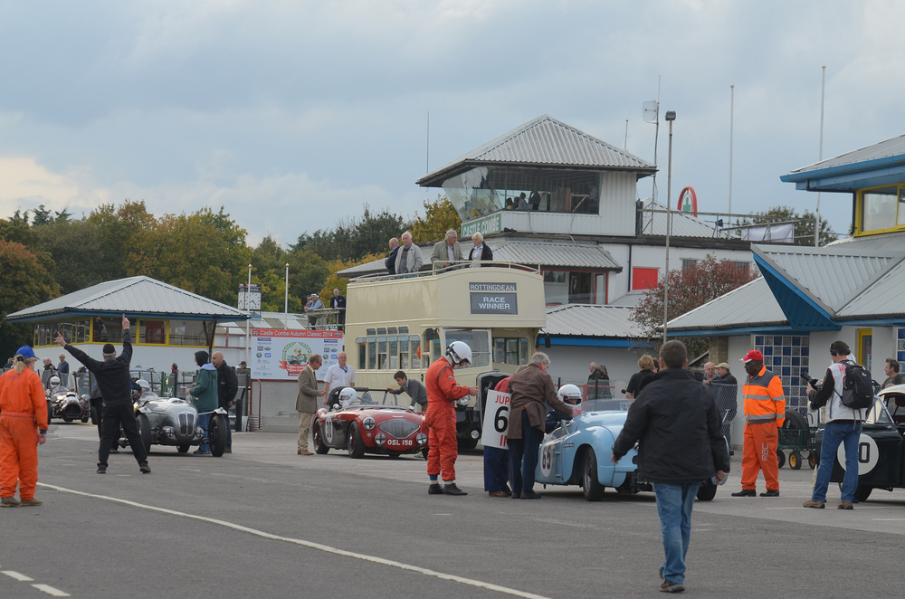 Always great to see the Jowett Jupiter out - Richard Gane and John Arnold change places. Behind, Keith Jenkins, driving the Austin Healey solo this time, waits patiently for his timekeeper to complete countdown, as does Ned Spieker In the Frazer Nash High Speed Model. To the left, much waving of arms heralds the arrival of John Ure in the Cooper Bristol.   Photo - Ollie Read