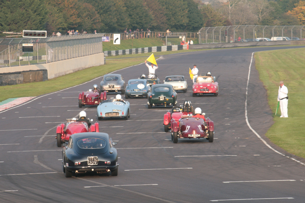 The cars form up on the grid, with Nick Ruddell, given no qualifying time taking his place at the back of the field in his Aston Martin DB2/4                                                 Photo - John Turner